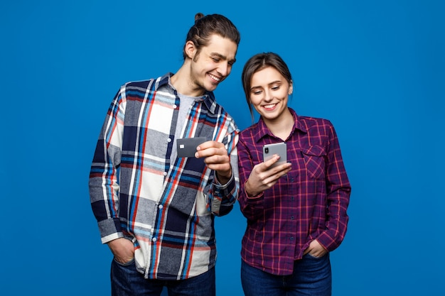 Beeld van glimlachende man en vrouw in vrijetijdskleding die en celtelefoons met creditcard bevinden zich houden