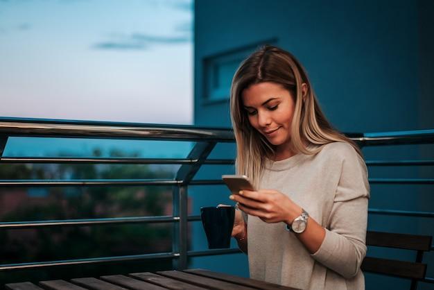 Beeld van glimlachende vrouw die smartphone gebruiken terwijl het drinken van thee of koffie op teracce.