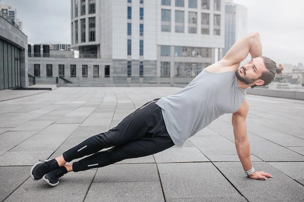 Beeld van goed-bilt jonge man die zijn lichaam uitrekt door oefeningen te doen