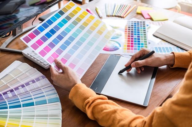 Beeld van grafische ontwerper die aan kleurselectie werkt en op grafiek trekt