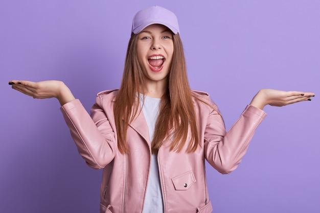 Beeld van het gelukkige studentenmeisje stellen met het uitspreiden van handen en het schreeuwen van iets