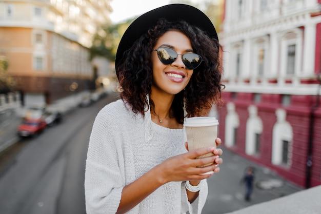 Beeld van het glimlachen van mooie zwarte in witte sweater en zwarte hoed die van koffie genieten om te gaan. stedelijke achtergrond.
