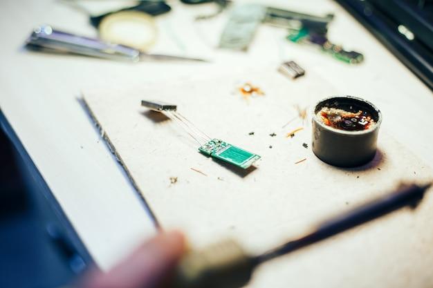 Beeld van ingenieur met soldeerbout die mechanisme herstelt