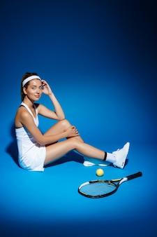 Beeld van jong fintess meisje dichtbij tennisracket en zitting op vloer