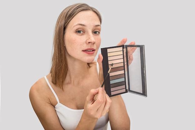 Beeld van jong model met en sproeten op en gezicht die kijken stellen. ze houdt pallete oogschaduwen vast en wijst met een kwast op één kleur. jonge vrouw ziet er mooi uit.