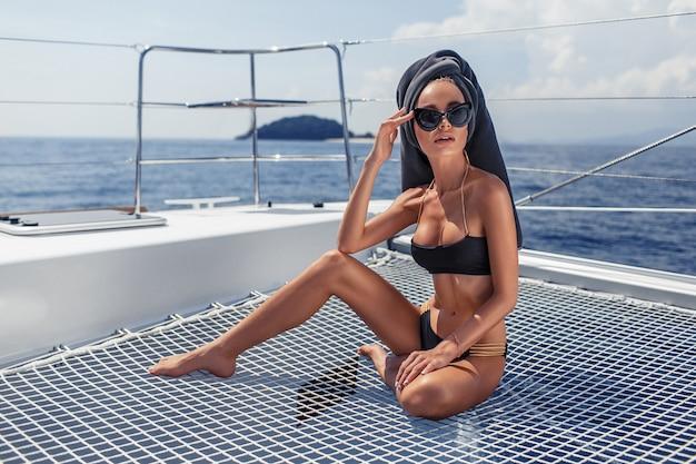 Beeld van jong verbazend meisje die zonnebril met handdoek in haar hoofdzitting op het jacht dragen