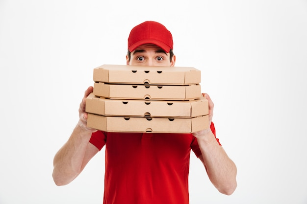Beeld van jonge bezorger in rode t-shirt en glb die gezicht behandelen met stapel pizzadozen, dat over witte ruimte wordt geïsoleerd