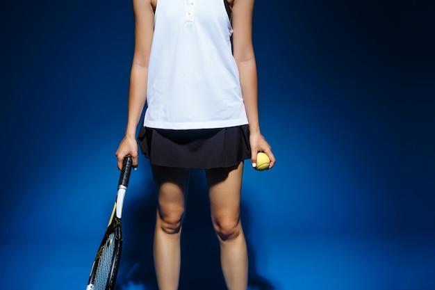 Beeld van jonge fintess het tennisracket en de bal van de meisjesholding