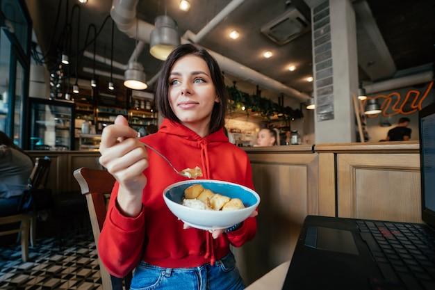 Beeld van jonge gelukkige glimlachende vrouw die pret heeft en roomijs in koffiewinkel of restaurantclose-upportret eet