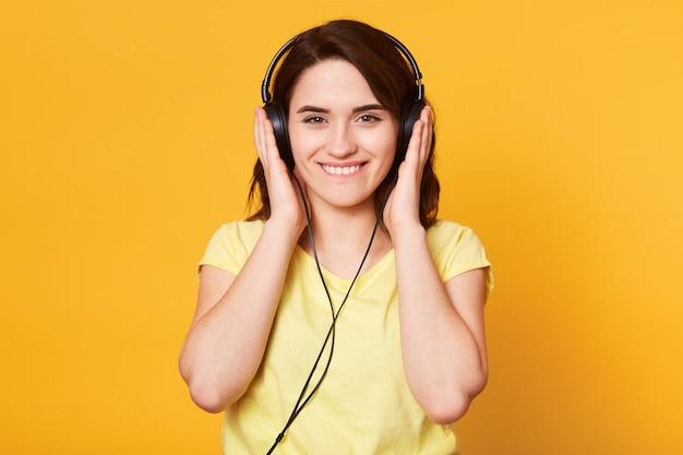 Beeld van jonge gelukkige vrouw die met hoofdtelefoons aan muziek luistert die over geel wordt geïsoleerd