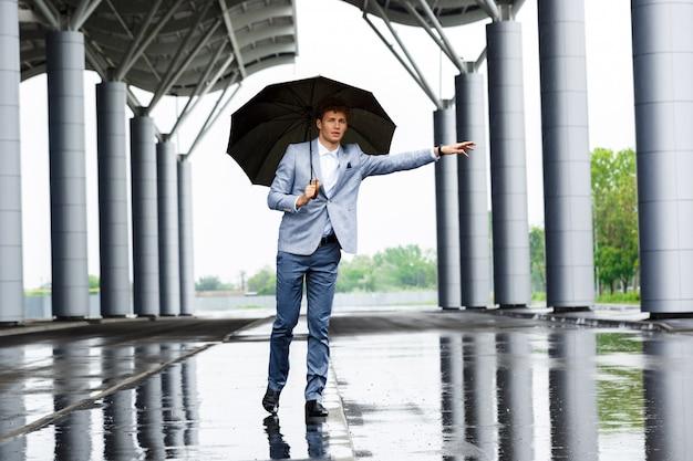 Beeld van jonge redhaired zakenman die de auto vangt en paraplu houdt bekijkend camera