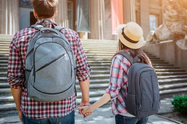 Beeld van jonge toeristen die zich voor treden bevinden. ze houden elkaars handen vast. reizigers dragen stenenzakken op hun rug en shirts in dezelfde kleur.
