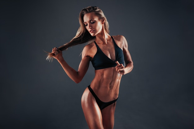 Beeld van jonge vrouw in sporten kleding die neer tegen zwarte achtergrond kijken
