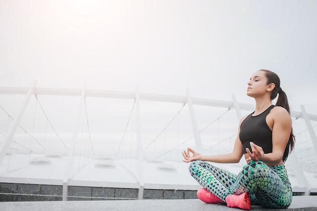 Beeld van jonge vrouwenzitting in lotusbloempositie en het mediteren