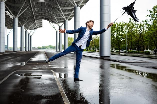 Beeld van jonge zakenman bij regenachtige terminal die gebroken paraplu vangt