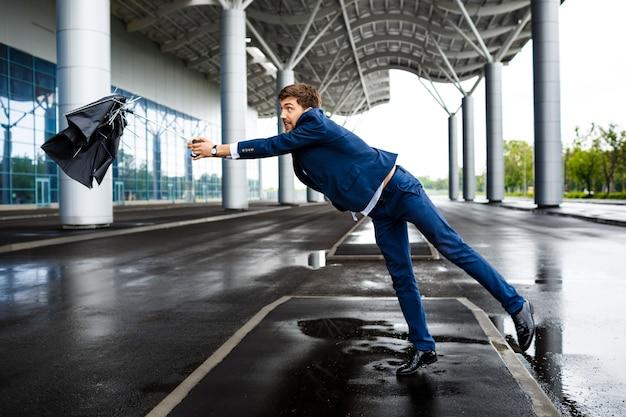 Beeld van jonge zakenman op regenachtige luchthaven die gebroken paraplu vangt