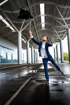 Beeld van jonge zakenman op regenachtige post die gebroken paraplu vangt