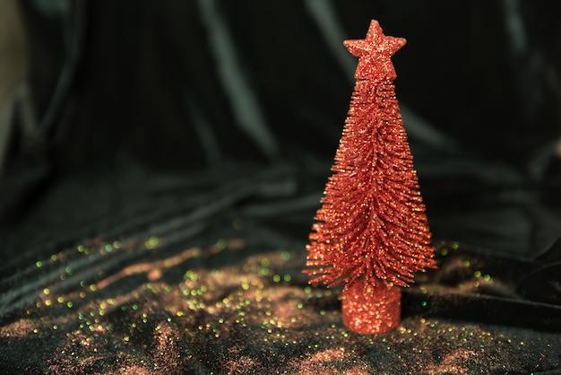 Beeld van kerstmislichten en rode pijnboomboom met ornamenten op zwarte achtergrond
