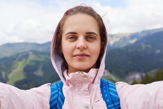 Beeld van knappe tevreden reisblogger die selfie maakt, rusttijd heeft, blij is met reisomstandigheden, plezier krijgt door actieve rust, bergen op haar achtergrond.