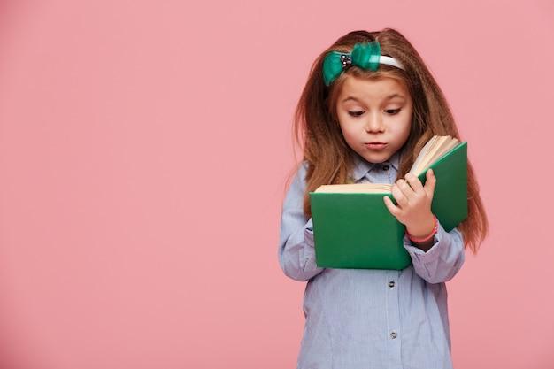 Beeld van leuk meisje dat met lang kastanjebruin haar interessant boek leest dat bij onderwijs wordt betrokken