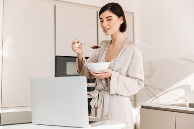 Beeld van leuke donkerbruine vrouw die badjas dragen die laptop met behulp van terwijl thuis het hebben van ontbijt, met graangewas en melk
