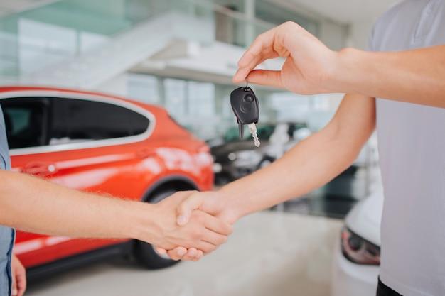Beeld van mannen die elkaars handen schudden. man op de rechter hold-toets in de linkerhand. ze staan voor rode auto en naast witte.