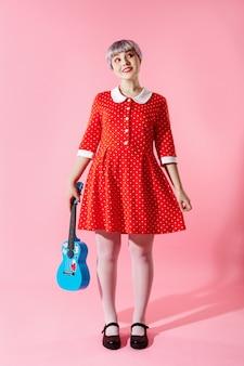 Beeld van mooi popachtig meisje met kort licht violet haar dat rode kleding draagt die blauwe ukelele over roze muur houdt