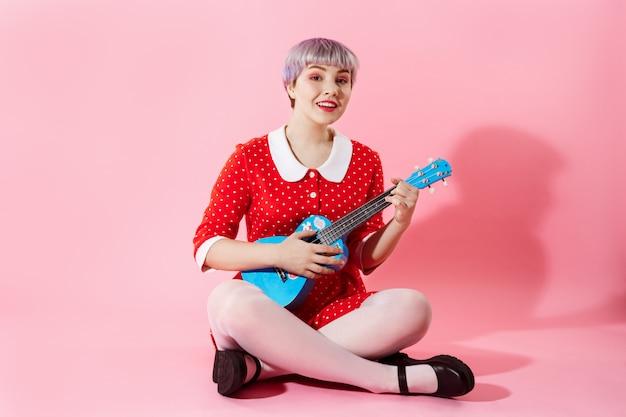 Beeld van mooi popachtig meisje met kort licht violet haar dat rode kleding draagt die blauwe ukelele over roze muur speelt