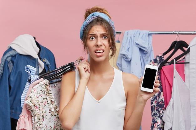 Beeld van mooie jonge europese vrouw die gefrustreerde en ongerust gemaakte blik heeft gehad omdat zij al haar geld aan haar accountant besteedde aan het kopen van nieuw kledingstuk, het houden van hagers met kleren en mobiele telefoon