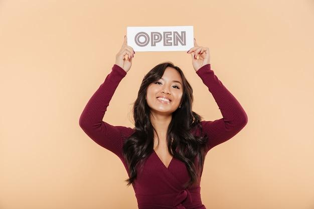 Beeld van mooie vrouw in het kastanjebruine teken van de kledingsholding met woord open lucht zijnd vriendelijk op perzikachtergrond