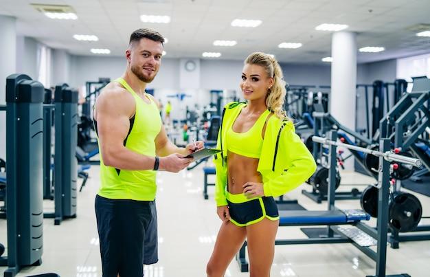 Beeld van persoonlijke geschiktheidstrainer en vrouwelijke cliënt in gymnastiek het stellen vooraan. gezond leven en fitness concept.