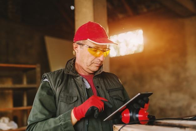 Beeld van rijpe oudere timmerman in beschermend uniform in zijn werkende garage die tablet bekijken.