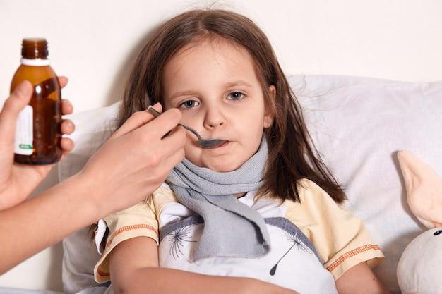 Beeld van slaperig ziek kind het drinken stroop, direct kijkend, hebbend blik, liggend in bed dichtbij haar stuk speelgoed