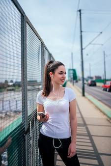 Beeld van sportieve meisje het luisteren muziek in openlucht, bij de stad.