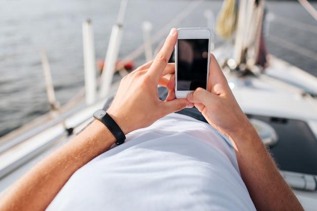 Beeld van telefoon in man handen. hij heeft er vertrouwen in. scherm is donker. telefoon is wit. jonge man ligt aan boord van de jacht.