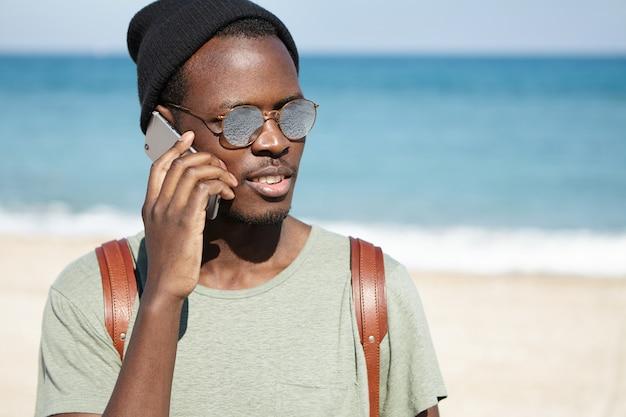 Beeld van trendy uitziende zwarte mannelijke toerist met knapzak, die hoed en zonnebril op zonnig weer draagt, die op mobiele telefoon spreekt