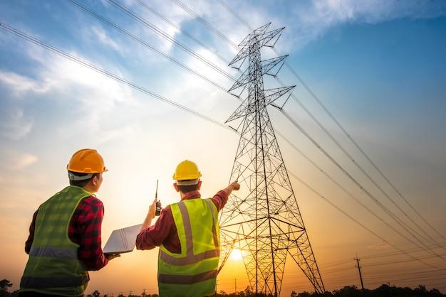 Beeld van twee elektrotechnici die het elektrische werk controleren met behulp van een computer die zich bij een krachtcentrale bevindt om het planningswerk bij hoogspanningselektroden te zien.