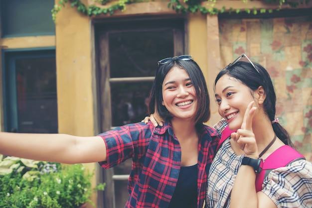 Beeld van twee jonge gelukkige vrouwenvrienden die zich in stedelijke stad bevinden. samen selfie maken.