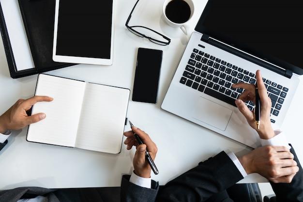 Beeld van twee jonge zakenlieden die computernotitieboekje gebruiken op vergadering in bureau, bedrijfs en bureauconcept