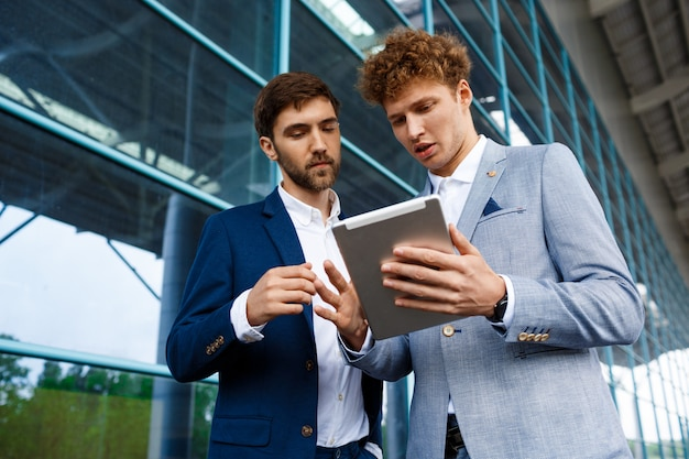 Beeld van twee jonge zakenlieden die op post spreken en tablet houden