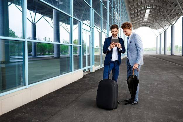 Beeld van twee jonge zakenlieden die op regenachtige post spreken en tablet houden