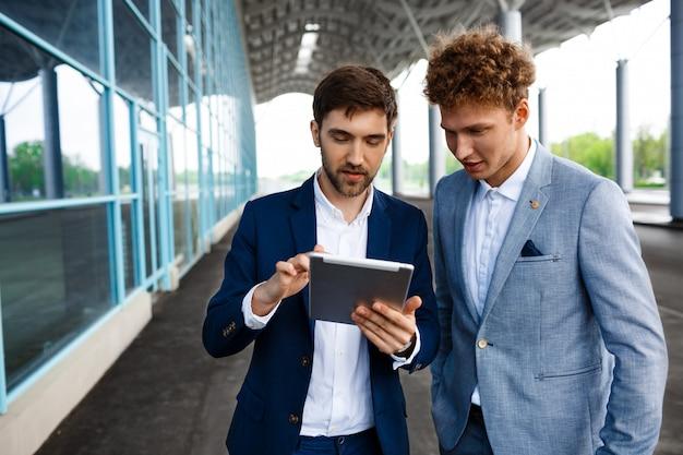 Beeld van twee jonge zakenlieden die op terminal spreken en tablet houden