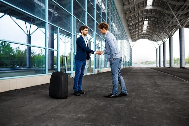 Beeld van twee jonge zakenlieden die samenkomen bij en handen schudden
