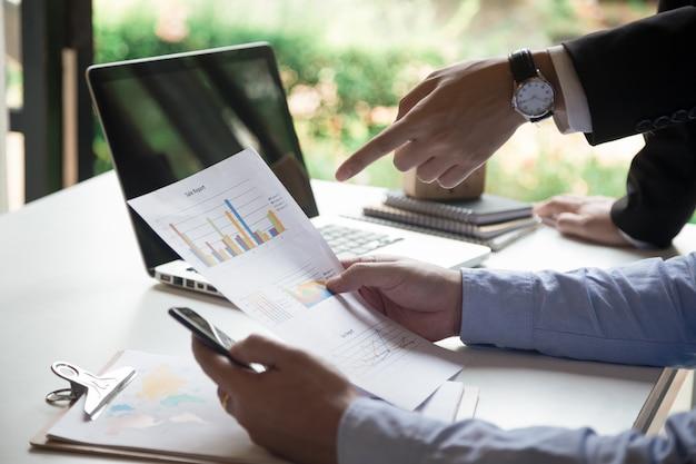 Beeld van twee jonge zakenlieden die touchpad op vergadering gebruiken