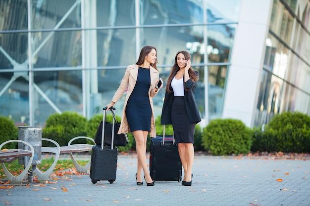 Beeld van twee joyous europese vrouwen die smartphone bekijken