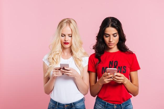 Beeld van twee vrij geconcentreerde vrouwen die haar smartphones over roze gebruiken