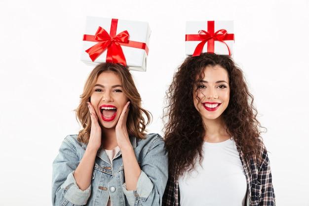 Beeld van twee vrolijke meisjes die giften op hun hoofden over witte muur houden