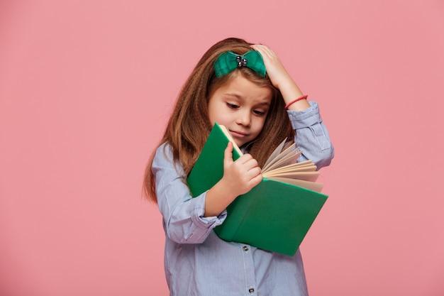 Beeld van vermakelijk meisje in overhemd dat haar hoofd grijpt terwijl het lezen van boek dat studie moe is