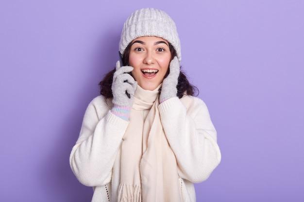 Beeld van verraste emotionele jonge dame die met donker krullend haar direct camera bekijken, smartphone dichtbij oor houden, opheffend haar handen