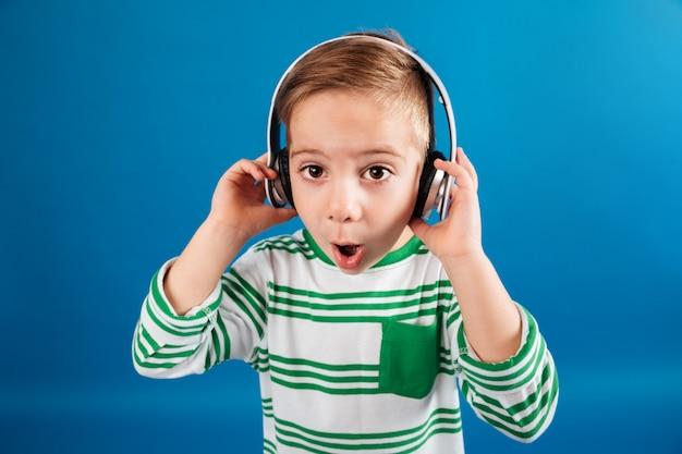 Beeld van verraste jonge jongen het luisteren muziek door hoofdtelefoon